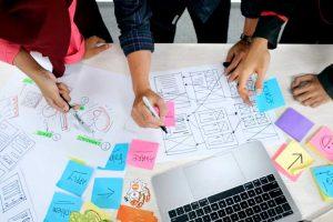Drei Personen arbeiten an einem Tisch, zeichnen und beschriften Klebezettel zum Thema UX.