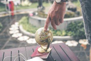 Ein Finger zeigt auf einen kleinen Globus.