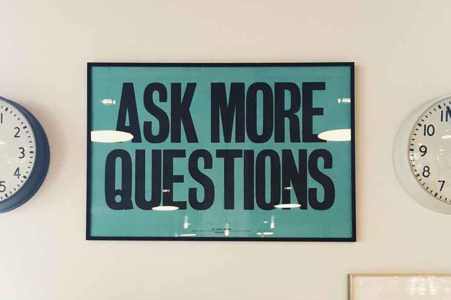 "Schild auf dem ""Ask more Questions"" steht."