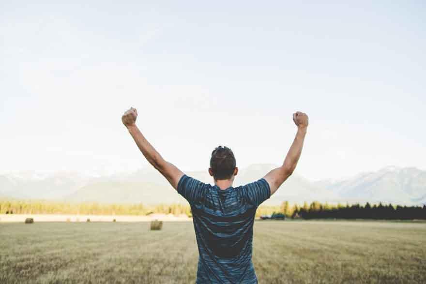 Mann steht mit erhobenen Händen in Siegerpose auf einem weitem Feld.