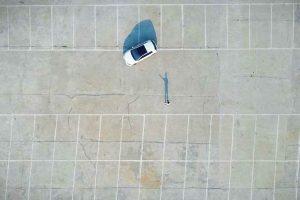 Ein großer, leerer Parkplatz und ein weißes Auto.
