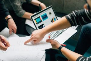 drei Personen arbeiten an einem Tisch mit einem Laptop und Dokumenten.