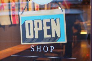 """Ein Schild an einer gläsernen Tür zeigt das Wort """"Open""""."""
