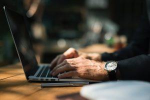 EIne Person tippt auf die Tastatur eines Laptops.