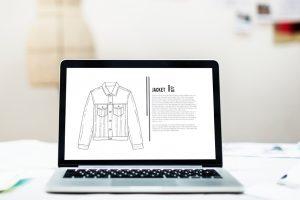 Laptop, der eine Zeichnung einer Jacke zeigt, steht auf einem Tisch.