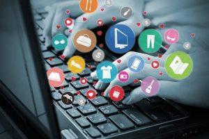 Frau an einem Laptop, aus dem Icons zum Online Shoppen erscheinen.