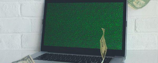 Ein augeklappter Laptop auf dem Geldscheine regnen.