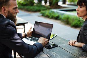 Zwei Personen sitzen mit Laptop an einem Tisch draußen und sprechen miteinander.