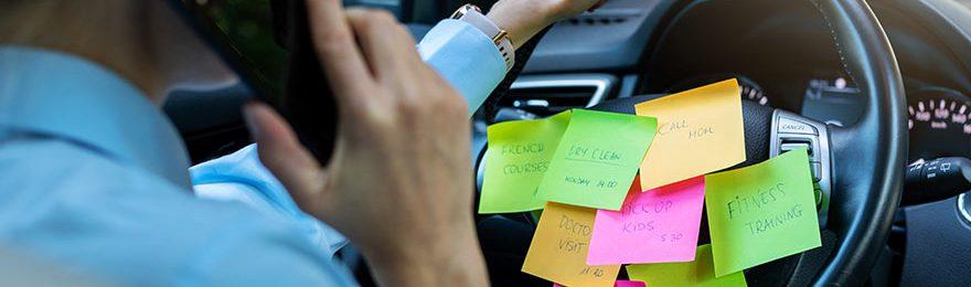 Eine Frau am Steuer telefoniert und hat mehrere bunte Notizzettel am Lenkrad befestigt.