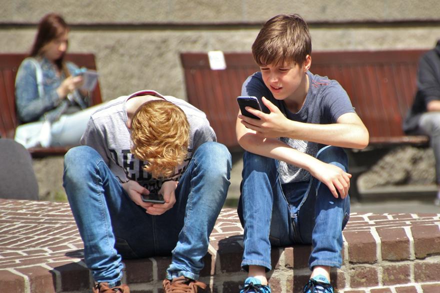 zwei Jungs ins Smartphone vertieft