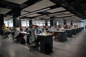 Mehrere Personen arbeiten an verschiedenen Computern in einer großen Halle.