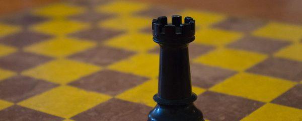 Nahaufnahme Schachfigur schwarzer Turm auf Schachbrett.