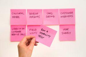 """Mehrere Pinke Notizzettel. Eine Hand hält einen auf dem """"Run a Usability test"""" steht."""
