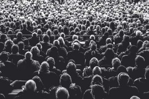 Voller Saal von Menschen, die in den Sitzreihen Platz genommen haben.