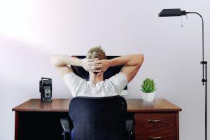 Ein Mann sitz mit hinterm Kopf verschränkten Armen an einem Schreibtisch.