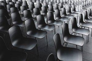 Schwarzweiß Foto von leeren Stuhlreihen.