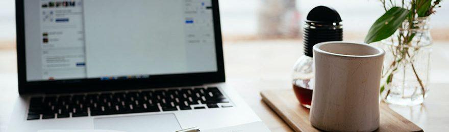 Ein Laptop, Notizbuch, Kaffeetasse und eine kleine Vase mit Blumen stehen auf einem Tisch.