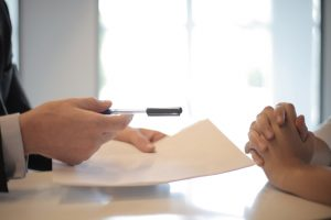 Zwei Personen sitzen an einem Tisch und unterhalten sich. Eine Person hält Stift und Papier in einer Hand.