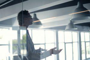 Ein Herr hinter einer Glaswand hält eine Rede.
