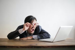 Mann sitzt verzweifelt vor seinem PC und schreit.
