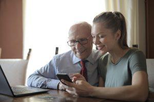Ein älterer Herr und eine junge Frau sitzen an einem Tisch mit einem Laptop und schauen auf ein Smartphone Display.