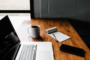 Laptop, Smartphone, Block und Kaffeetasse auf einem Tisch.
