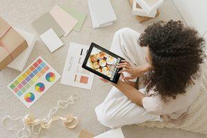 Dame sitzt vor Farbmustern und betrachtet einen Online Shop