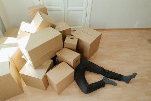 EIn Mensch liegt unter Paketen begraben auf dem Boden.