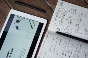 Notizbuch, Stift und Tablet auf einem Tisch