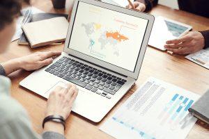 Laptop zeigt Weltkarte mit verschiedenen Makierungen. Weitere Schreibutensilien und Datenauswertungen sind auf dem Tisch verteilt-
