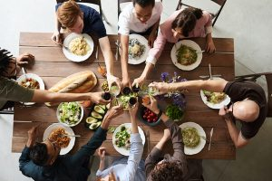 Mehrere Personen an einem großen Tisch essen zusammen und stoßen mit ihren Glässern an.