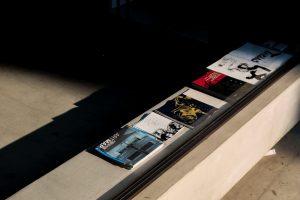 Kataloge aufgereiht auf einem Tisch.