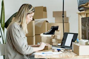 Frau sitzt am PC und arbeitet. Im Hintergrund sind viele Kartons und Produkte zu sehen.