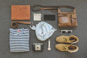 Kleidung und Accessoires auf dem nebeneinander aufgereiht.