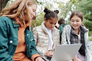 Drei Jugendliche sitzen draußen vor einem Laptop.