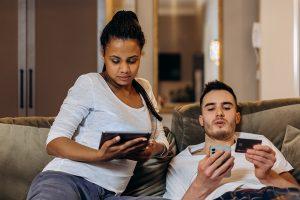 Zwei Personen shoppen mit einem Tablet und einem Smartphone auf einer Couch.