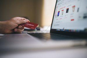 Das Bild zeigt einen Online Shop auf einem Laptop und eine Kreditkarte in einer Hand.