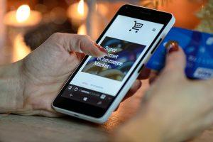 Smartphone in einer Hand zeigt ein Online Shop.