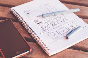 Smartphone und Notizbuch mit UI/UX Zeichnungen auf einem Tisch