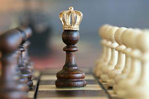 Eine Schachfigur mit einer goldenen Krone auf einem Schachbrett.