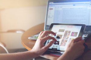 Eine Hand scrollt durch einen Online-Shop auf ein Ipad.