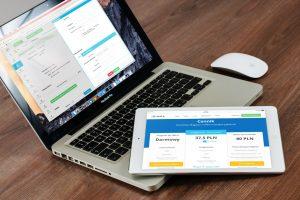 Laptop mit einem geöffneten Online Formular, wie auch ein Tablet auf einem Tisch.