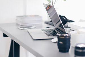 Schreibtisch mit Laptop, Smartphone und anderen Utensilien.