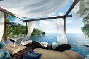 Laptop liegt auf einem Strandbett am Meer.
